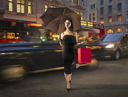 chicas comprando: Ir de compras en una noche de lluvia Foto de archivo