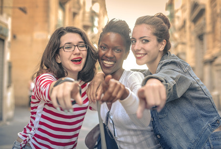 happy young woman: Three girl pointing at something Stock Photo