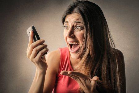 Angry woman checking her phone Stockfoto