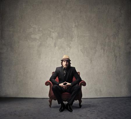 hombre con sombrero: poderoso hombre sentado en una silla roja