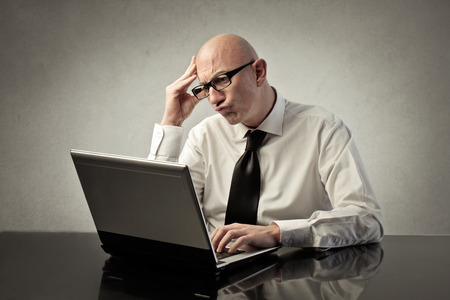 pc: Worried businessman using a pc