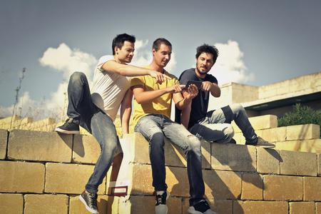 hombres jovenes: Tres hombres jóvenes sentados juntos