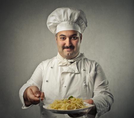 plato del buen comer: Cocinero que muestra un plato de pasta Foto de archivo