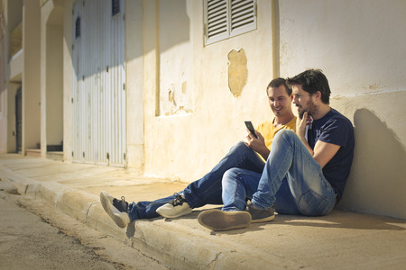 sidewalk talk: Two men sitting on the ground Stock Photo