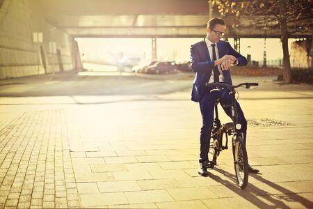 elegant business man: Businessman riding a bike