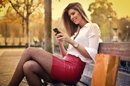 Elegante vrouw, zittend op een bankje