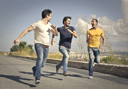 run way: Three men running down a street Stock Photo