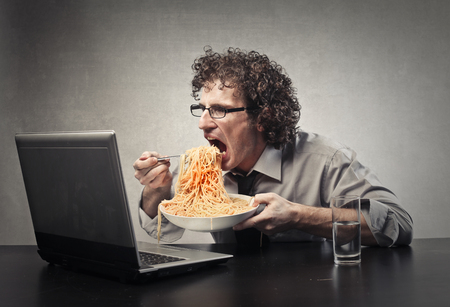 loco: Hombre hambriento viendo una película en su computadora portátil Foto de archivo