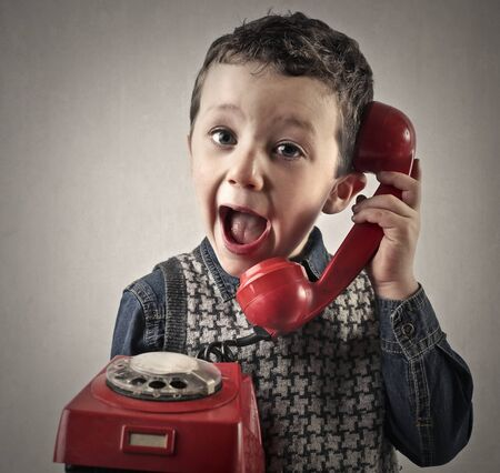 speak: Young child using a retro styled red phone