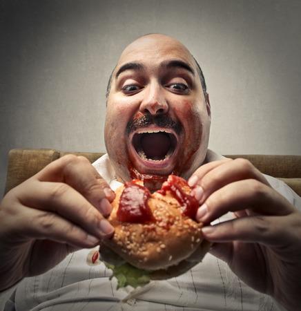 Hombre gordo que come una hamburguesa