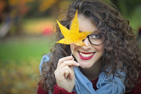 glasses eye: Woman holding an autumn leaf