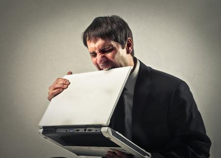 Man biting the screen of his laptop