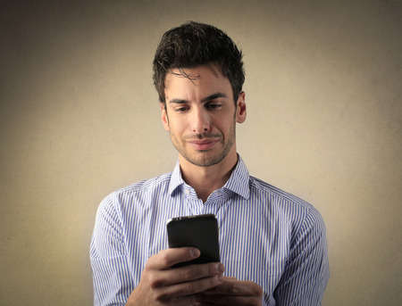 disappoint: Man using a smartphone Stock Photo