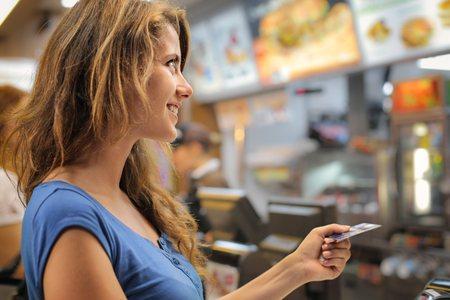 comida rapida: Mujer que paga en un restaurante de comida rápida Foto de archivo