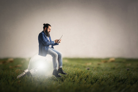 Creative man sitting on a bulb Stock Photo