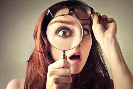 anteojos: Mujer joven que mira a través de la lupa Foto de archivo