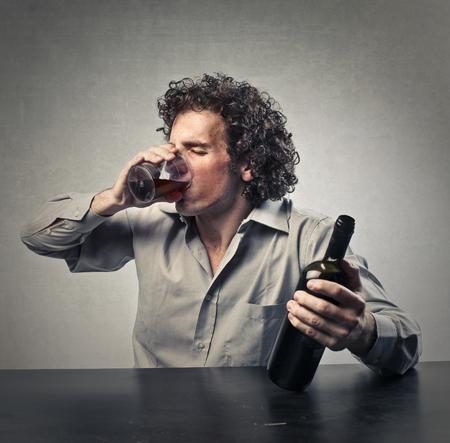 loco: Hombre que bebe una botella entera de vino Foto de archivo