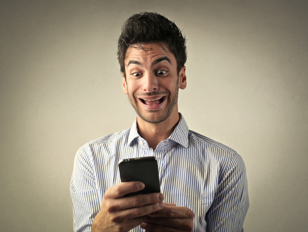 jubilate: Excited man reading a text message