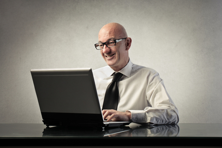 pc: satisfied businessman working at pc Stock Photo