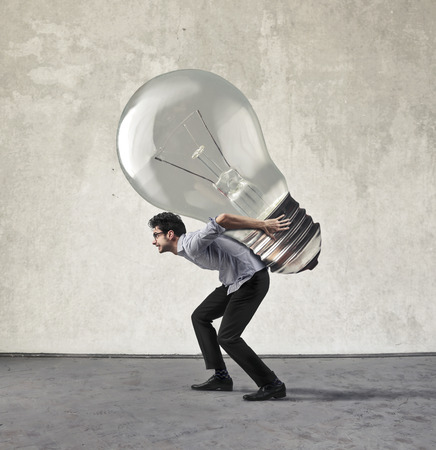 Employee carrying a heavy bulb Stock Photo