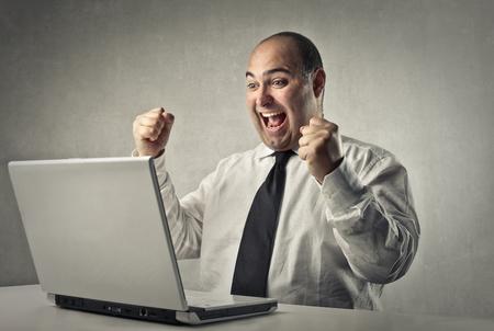persona leyendo: Feliz el hombre delante de un ordenador portátil