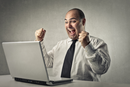 person reading: Happy man in front of a laptop Stock Photo