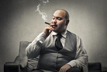 Homem gordo fumando um charuto