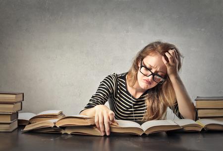 étudiant Bored lisant un livre Banque d'images