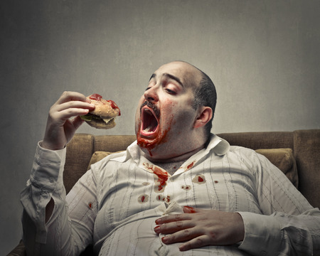 MEN: Fat man eating a sandwich