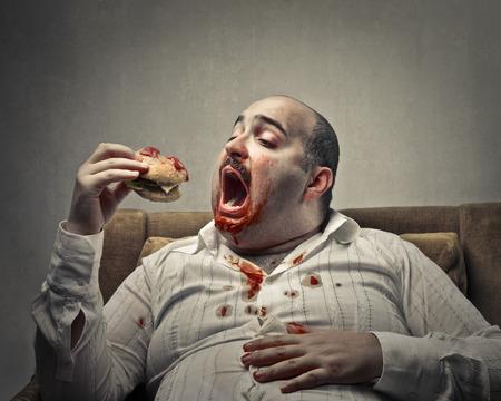 Hombre gordo comiendo un sándwich