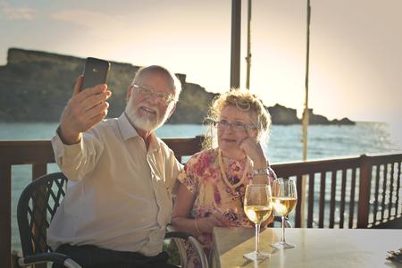 高齢者のカップルが海辺で selfie をやって
