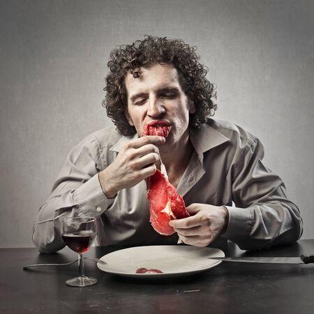 hombre rojo: Hombre comiendo carne cruda Foto de archivo