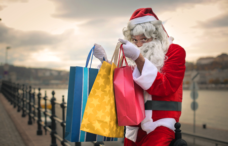 christmas hat: Santa Claus holding shopping bags Stock Photo