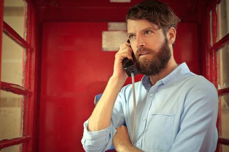 phone calls: Bearded man in a phone box Stock Photo