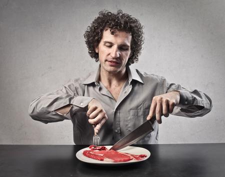 hombre comiendo: Hombre comiendo carne cruda Foto de archivo