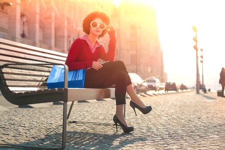 sunset city: Fashionable woman sitting in the sunshine
