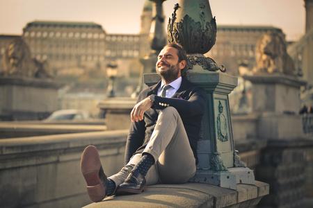 屋外に座って満足している実業家