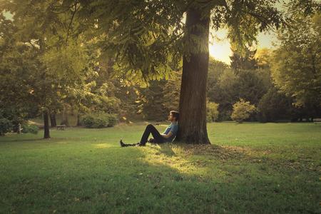 Man zit onder een boom in het park Stockfoto