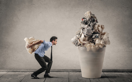 carry on: Businessman throwing sheets of paper in the trash can Stock Photo