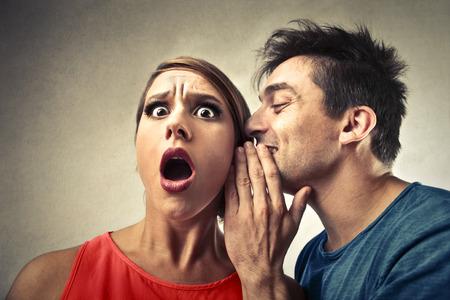 oido: El hombre susurrando en el o�do de una mujer Foto de archivo