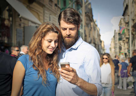 business man phone: Couple looking at the smartphone Stock Photo