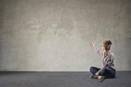 Femme assise sur l'écriture du sol sur un mur Banque d'images