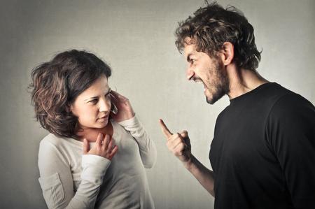 Zorniger Mann schreiend in Richtung seiner Freundin Standard-Bild