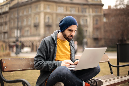 writes: Creative man sitting on a bench Stock Photo
