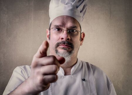 lay off: Severe cook pointing at someone