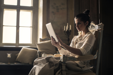 flawed: Beautiful woman reading from a tablet Stock Photo