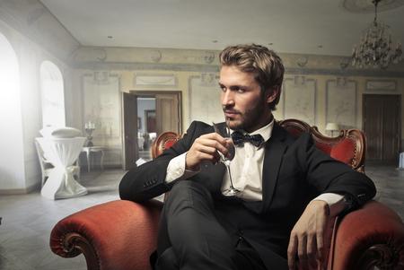 Przystojny mężczyzna siedzi w eleganckim pokoju