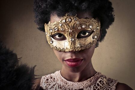 african mask: Beautiful masked young woman Stock Photo