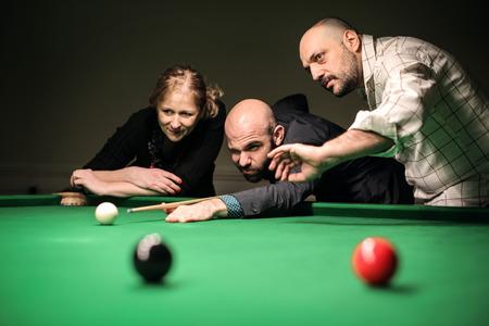 pool table: Three friends playing billiard