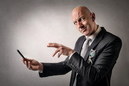 allusion: Businessman trying to use a smart phone Stock Photo